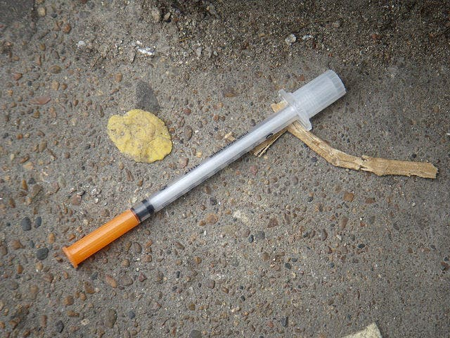 Heroin needle found in the gutter. Credit: Wikimedia Commons.