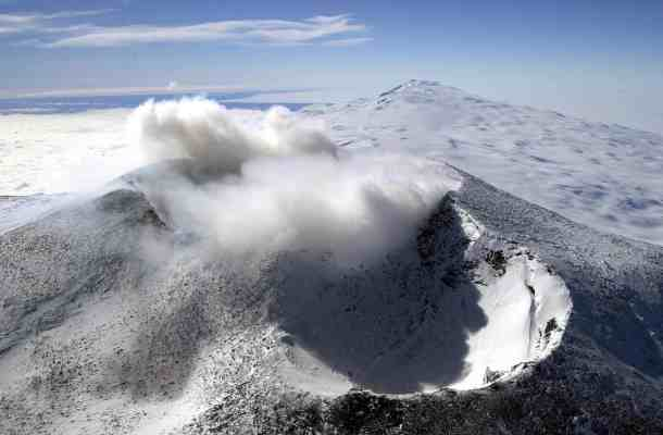 Aerial photo of Mount Erebus gushing smoke and ash from Ross Island, Antarctica. Credit: Wikimedia Commons.