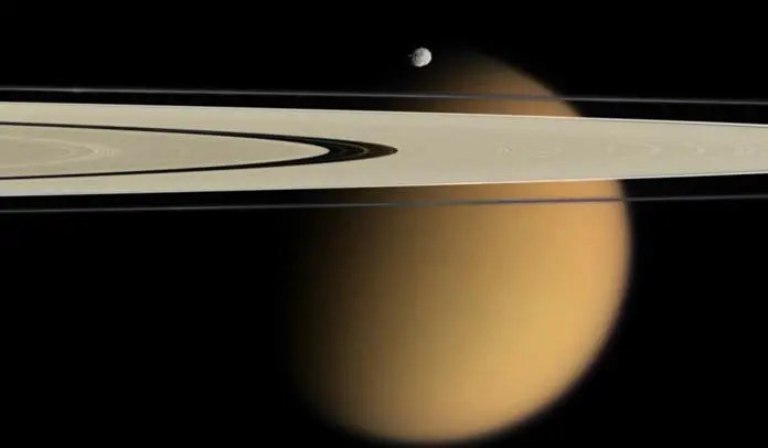 Cassini delivers this stunning vista showing small, battered Epimetheus and smog-enshrouded Titan, with Saturn's A and F rings stretching across the scene. Credit: NASA.