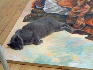 The cat sleeps on a painting.