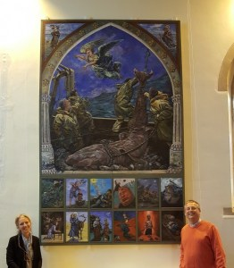 painting of the legend of St Michael and 12 small paintings about life journeys and pilgrimage from the old and new testaments this painting hangs in All Saints Church Marazion Cornwall shows artist Zoe Cameron and Canon Nigel Marns