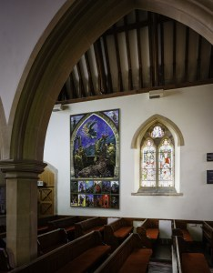 Interior of All Saints Church Marazion, Cornwall showing pews , an arch and a large painting on the wall.