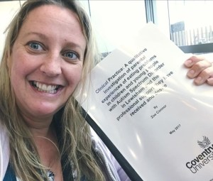 A picture of a white brunette woman holding her dissertation dated 2017