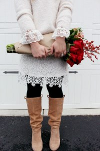 Blogger Zoe Namey from Zoe With Love shows how to wear white lace in winter styling a cropped sweater, black tights and tall boots.