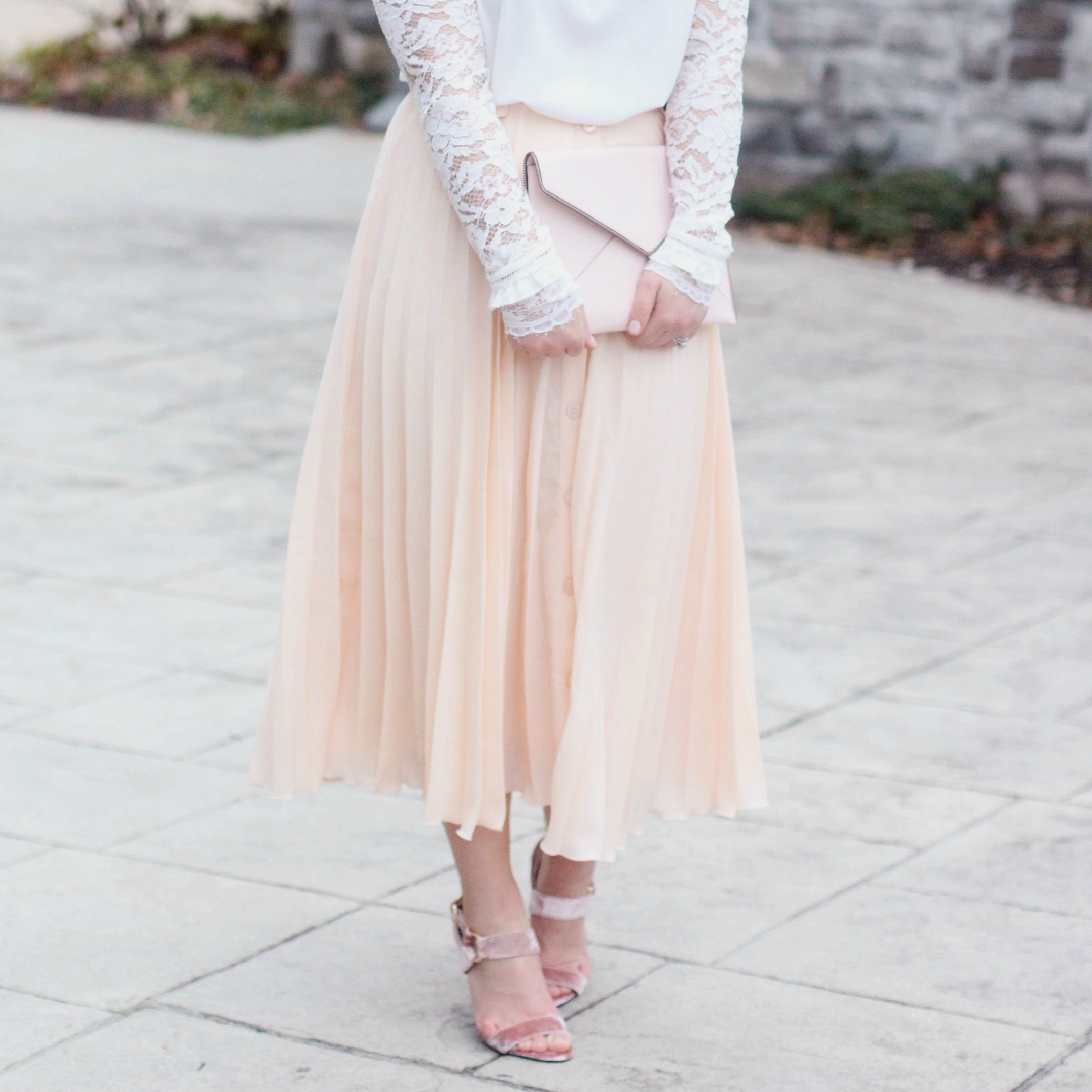 Zoe With Love styles this romantic look featuring a white lace top and pleated midi skirt., accessorizing with a simple envelope clutch and velvet heels.