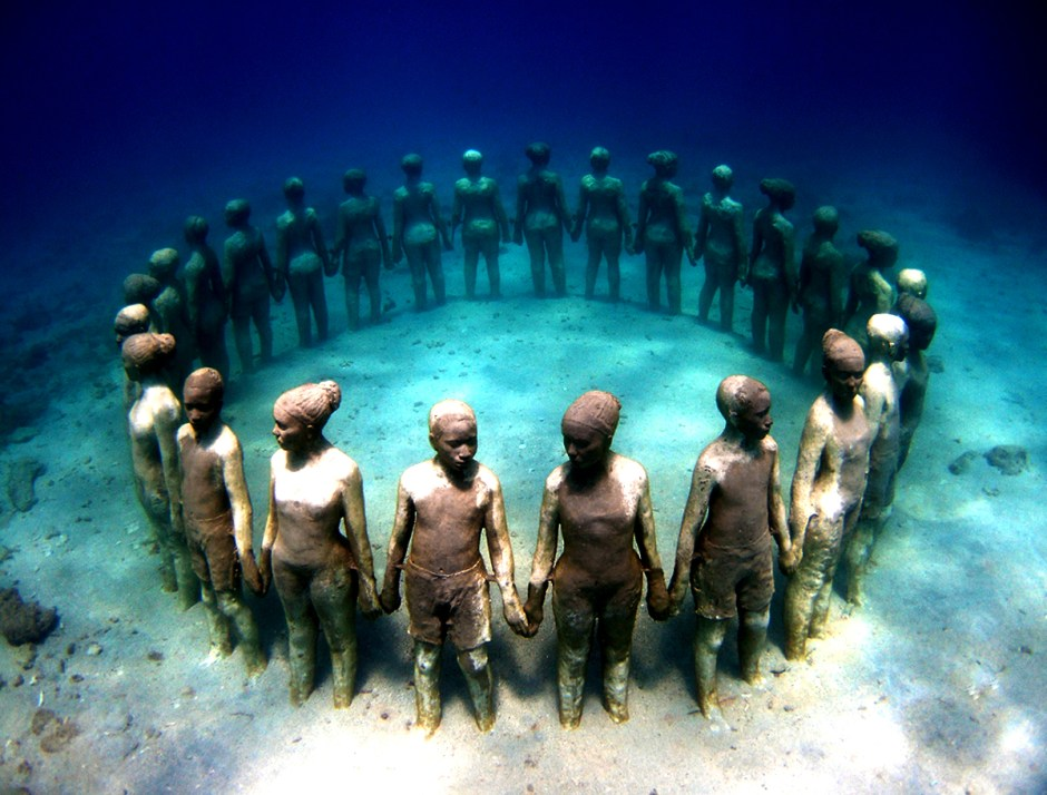 "JULY 2015 | JASON deCAIRES TAYLOR Underwater Museum in Cancun -- ""Silent Evolution"" underwatersculpture.com Bio:  ""Born in 1974 to an English father and Guyanese mother, Taylor grew up in Europe and Asia, where he spent much of his early childhood exploring the coral reefs of Malaysia. Educated in the South East of England, Taylor graduated from the London Institute of Arts in 1998 with a BA Honors in Sculpture and went on to become a fully qualified diving instructor and underwater naturalist. With over 20 years diving experience under his belt, Taylor is also an award winning underwater photographer, famous for his dramatic images, which capture the metamorphosing effects of the ocean on his evolving sculptures."""