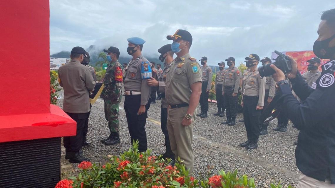 Kapolres Kepulauan Anambas saat Menyematkan Pita Tanda Pelaksanaan Operasi kepada Perwakilan yang ditunjuk dari TNI, Polri dan Satpol PP