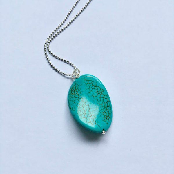Lange ketting met edelsteen turquoise gedraaide ovaal zilverkleurig