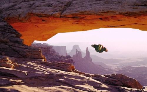 iron man flying through a natural arch