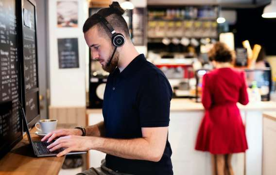 Young man with headphones and laptop indoors in cafe, working