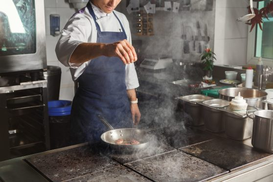 Male chef roasting and seasoning meat at professional restaurant kitchen. Man in uniform busy at work