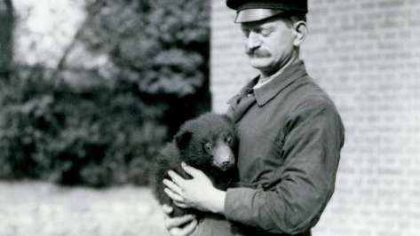 1921 - A Keeper holds a Sloth Bear cub at London Zoo (c) ZSL