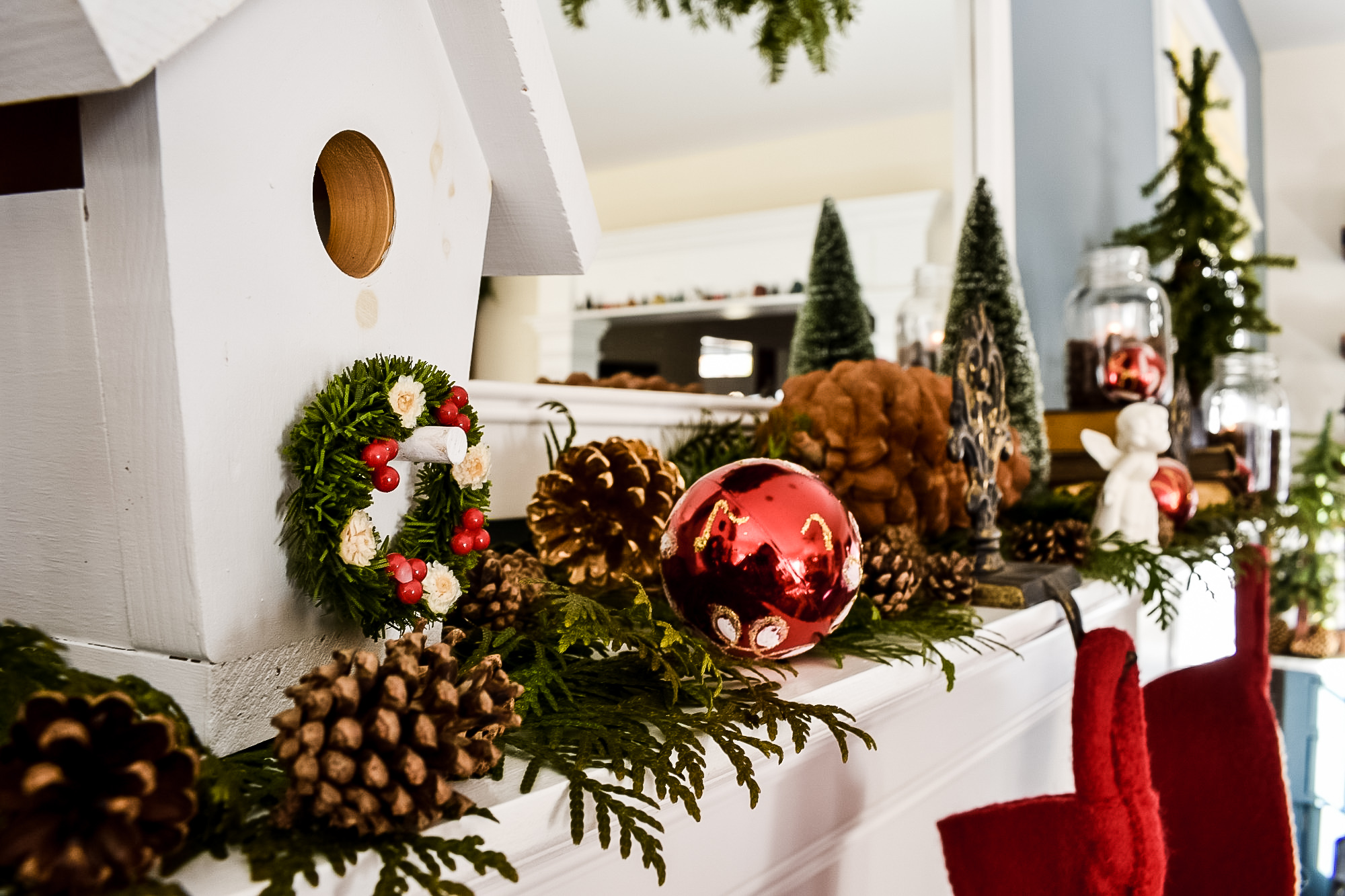 bird's house, pinecones, greenery and red ornaments on a Christmas mantel