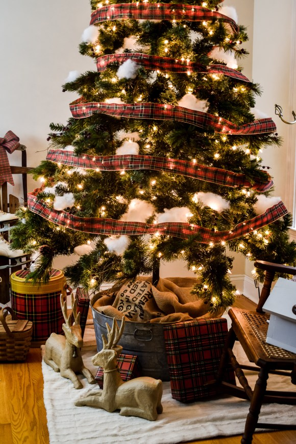 rustic Christmas tree decorated with plaid ribbon and faux snow in a galvanized tub