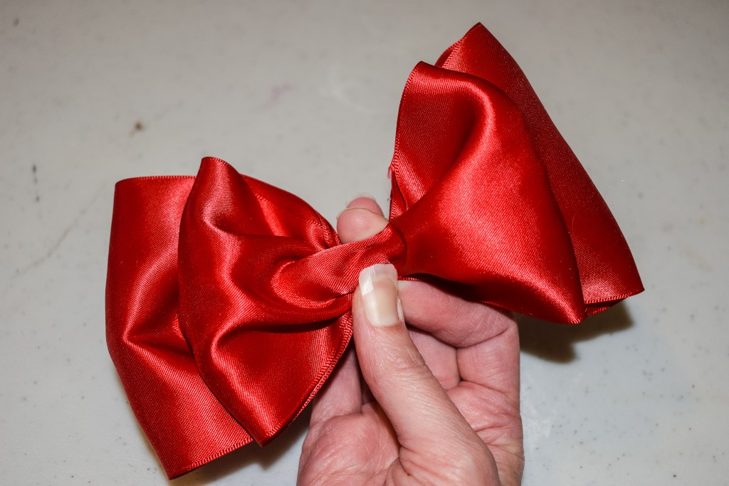 pinching two red ribbons in the middle to form a bow