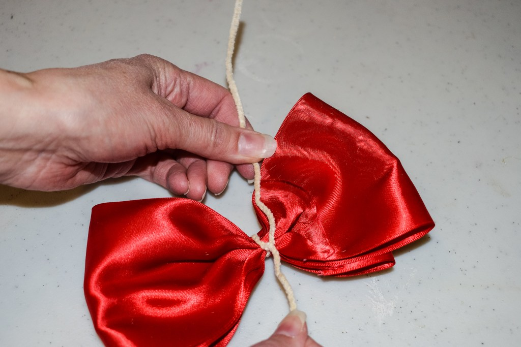 attaching a pipe cleaner in the middle of a red bow