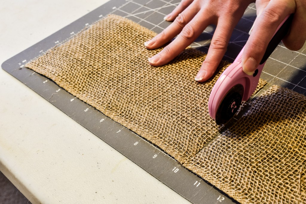 Cutting a ten inch strip of burlap on a cutting mat with a rotary cutter
