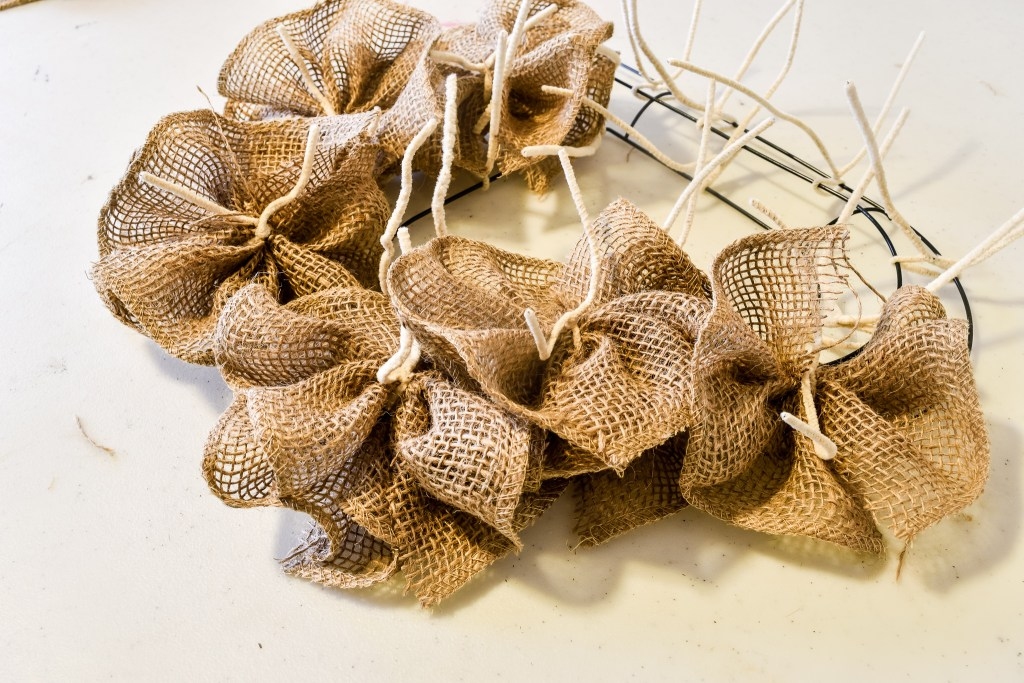 heart wreath form halfway covered with burlap flowers