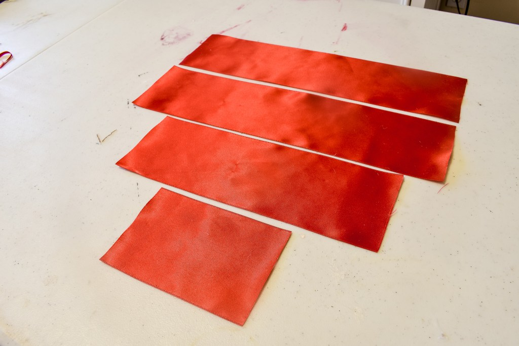 four strips of cut red ribbon for a DIY bow