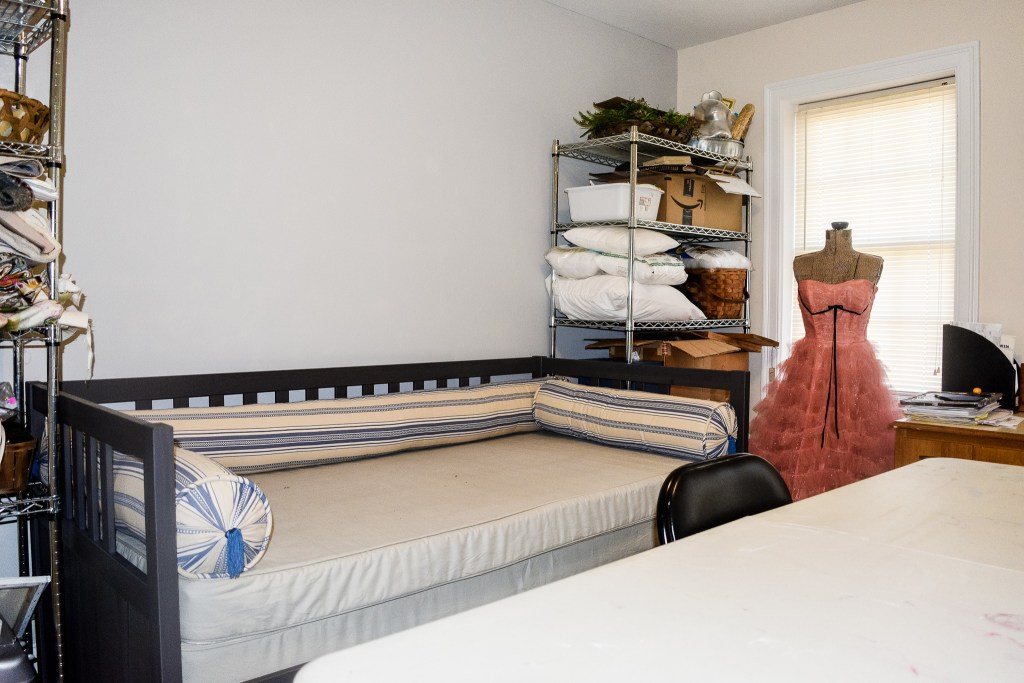 unmade daybed and disorganized craft room shelves