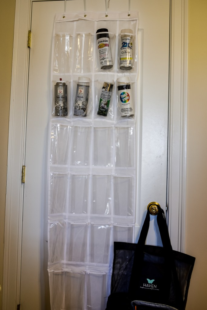 over the door shoe rack used to hold spray paint in an organized craft room