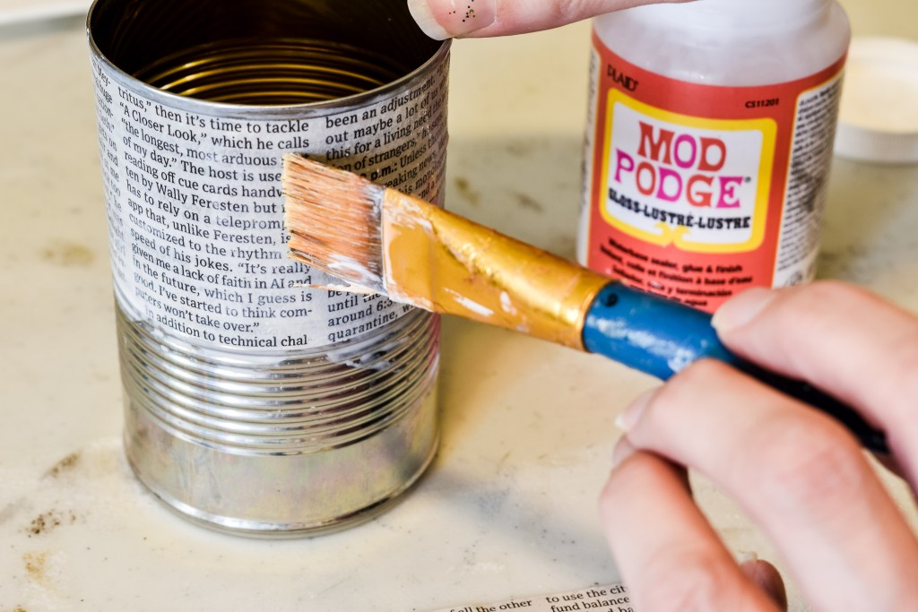 applying mod podge to a book page diy tin can decor craft project