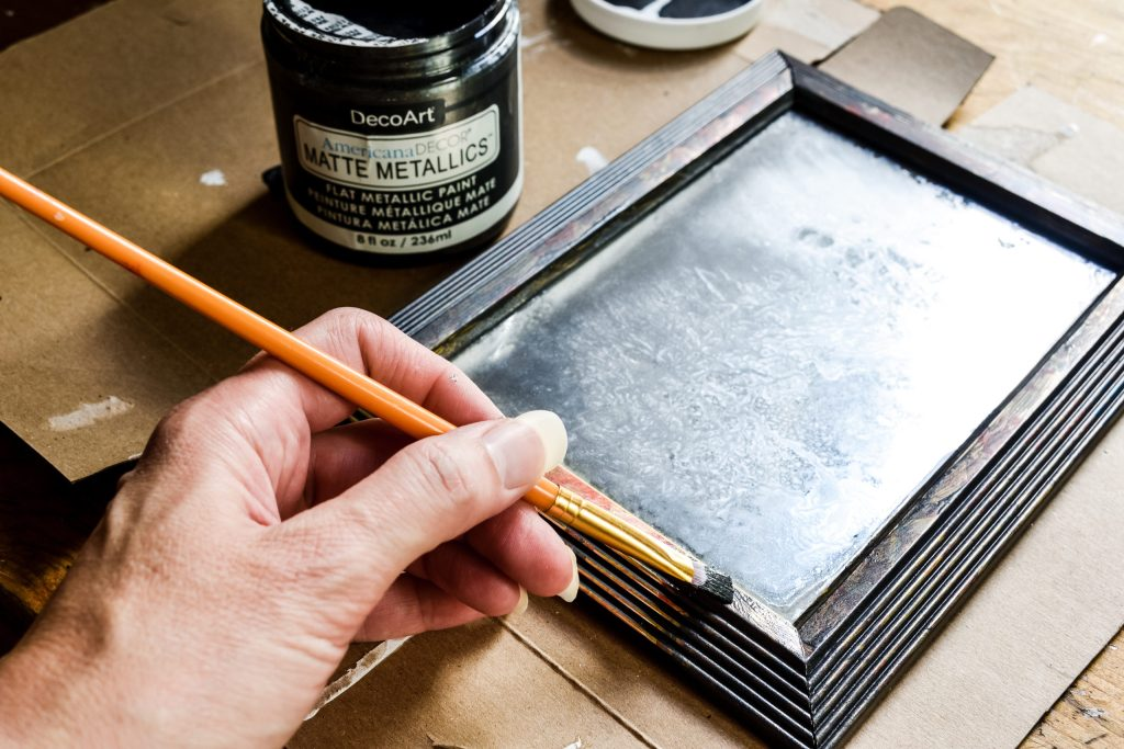 painting a frame with dark grey paint