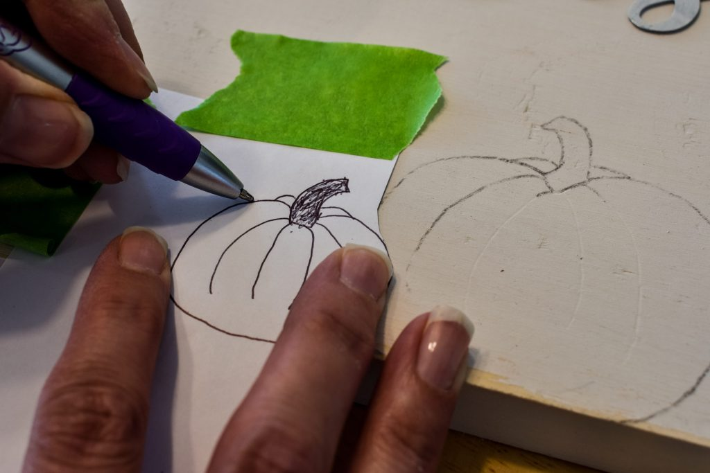 tracing a pumpkin drawing onto a painted wooden board used as a sign