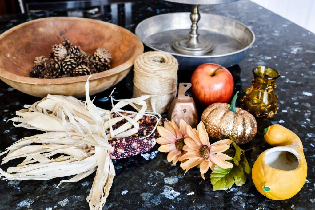 Indian corn, pinecones, apple, jute twine, copper bell, faux flowers, glitter pumpkin, and squash planter