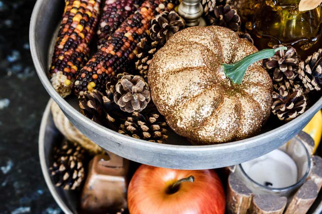 Indian corn, pinecones, glitter pumpkin, apple, copper bell and candle