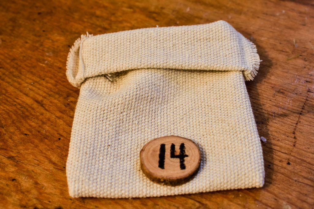 drop cloth bag with a wood slice and the number 14 glued to the front