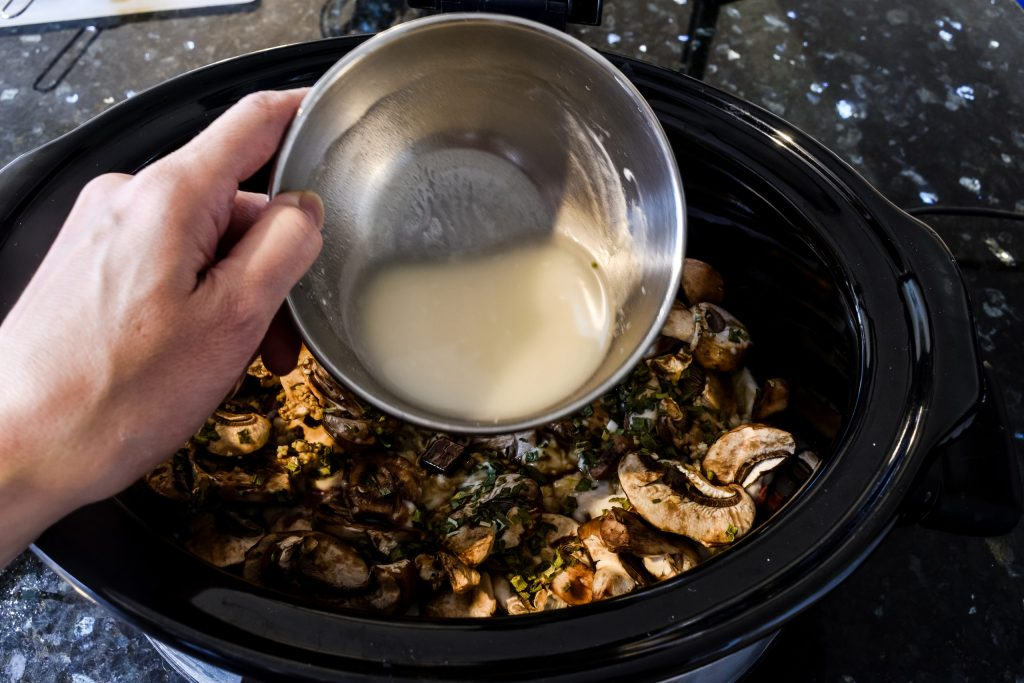 adding a mixture of white cooking wine and flour to a crock pot