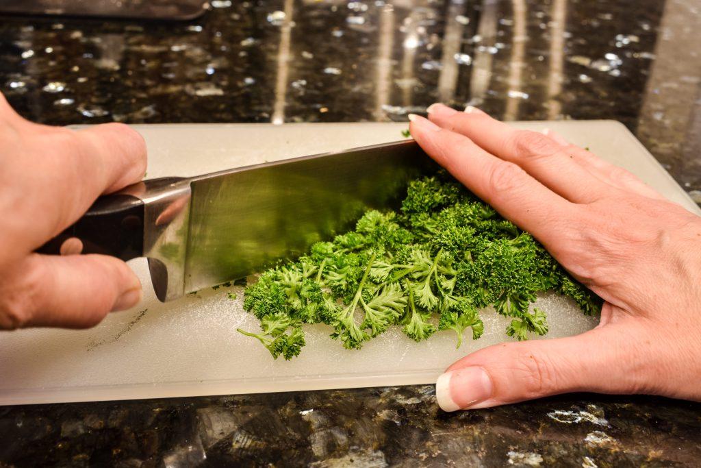 chopping curly parsley on a cutting board