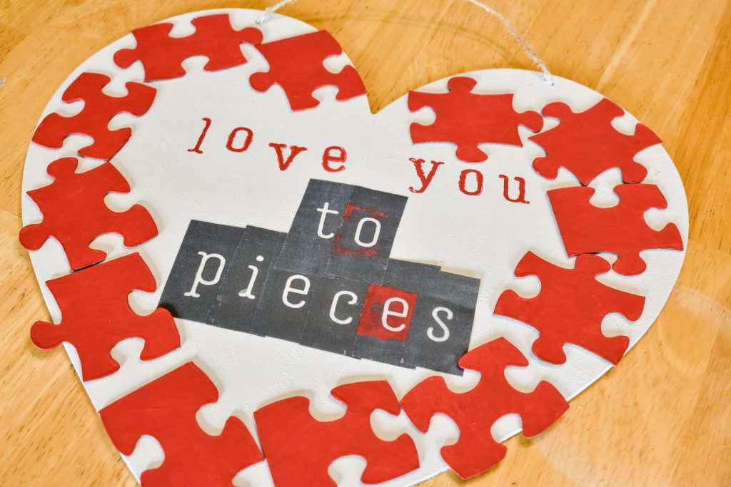"""stencils in the middle of a white painted wooden heart with the phrase """"love you to pieces"""""""