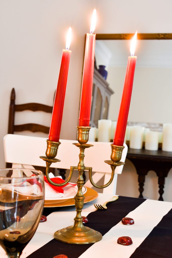 brass candelabra with three lit red taper candles
