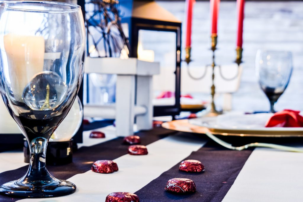 red Dove chocolates sprinkled on a black and white striped tablecloth on a Valentine's Day in Paris tablescape