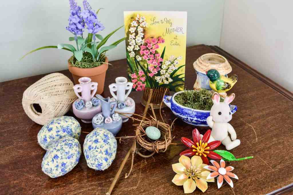 faux potted lavender, a vintage greeting card, mini bud vases, fabric covered Easter eggs, vintage floral brooches, a moss filled trinket dish, and a mini bunny
