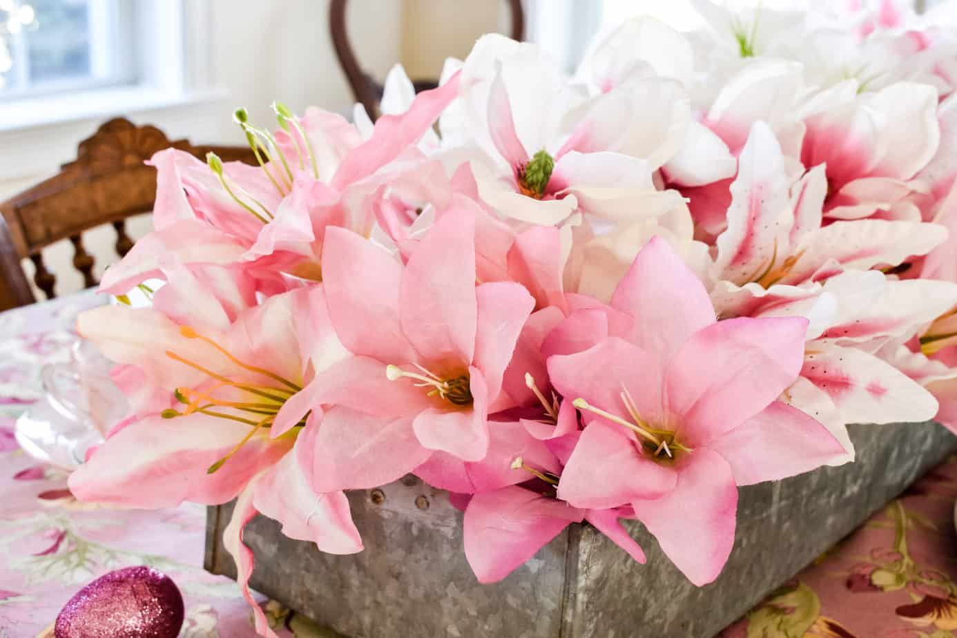 pink and white faux lilies in a long galvanized metal planter on a pink Easter tablescape