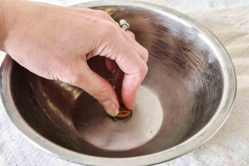 glueing pennies to the bottom of an aluminum bowl with Gorilla Glue