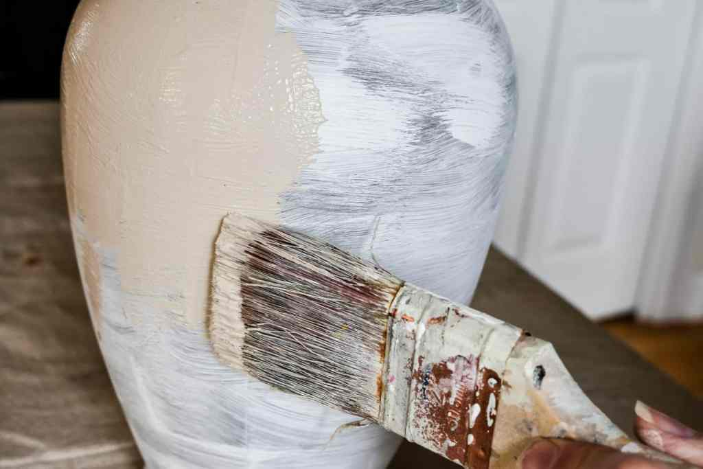 painting a large vase with a mixture of chalk paint and baking soda