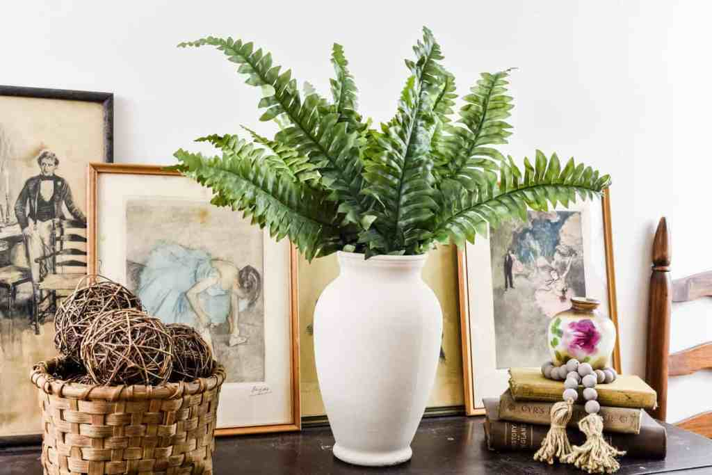 Faux textured clay vase diy filled with ferns and styled on a table