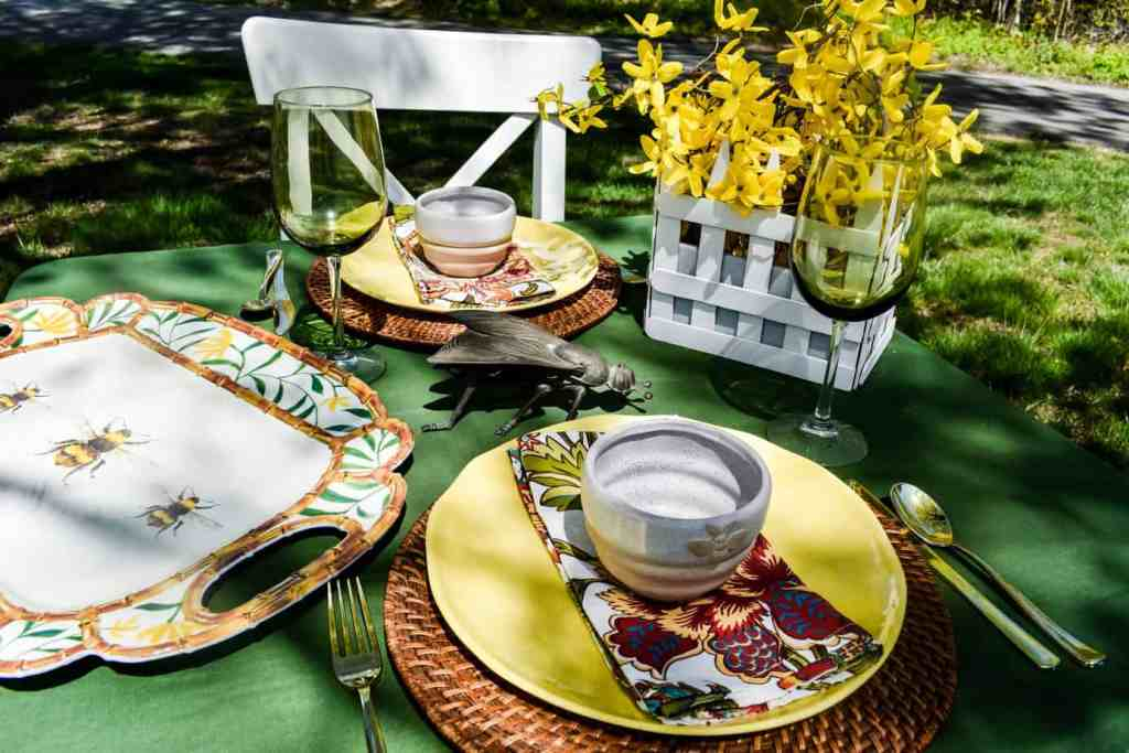 outdoor bee themed tablescape with a green tablecloth, yellow plates and bee motif tableware
