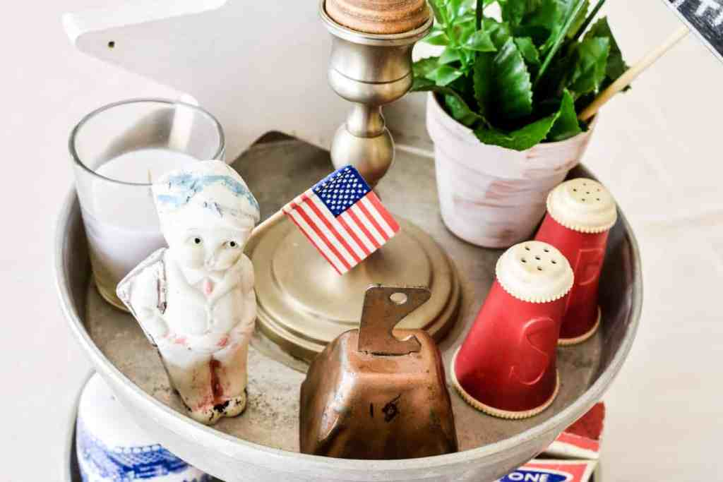 vintage and decorative items arranged in the top of a vintage patriotic home decor tiered tray