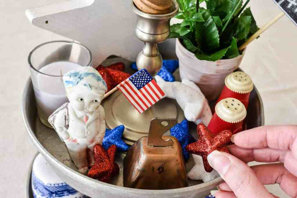 putting glittered red white and blue stars into the top of a vintage patriotic home decor tiered tray