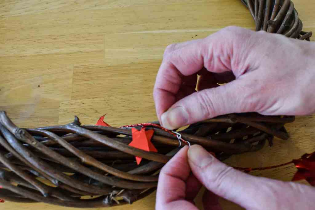attaching a red star garland to a grapevine wreath form with silver wire florist wire