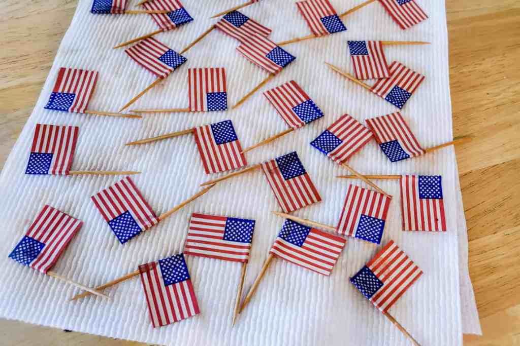 mini paper American flags drying on a paper towel after being tea dyed