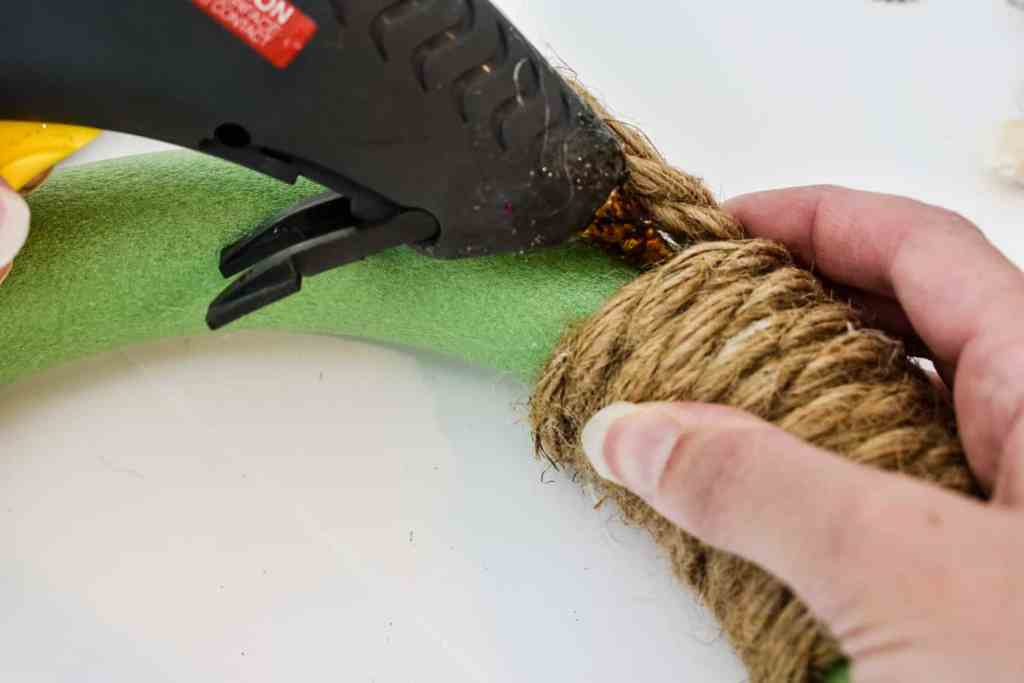 winding jute around a foam wreath form and securing it in place with hot glue