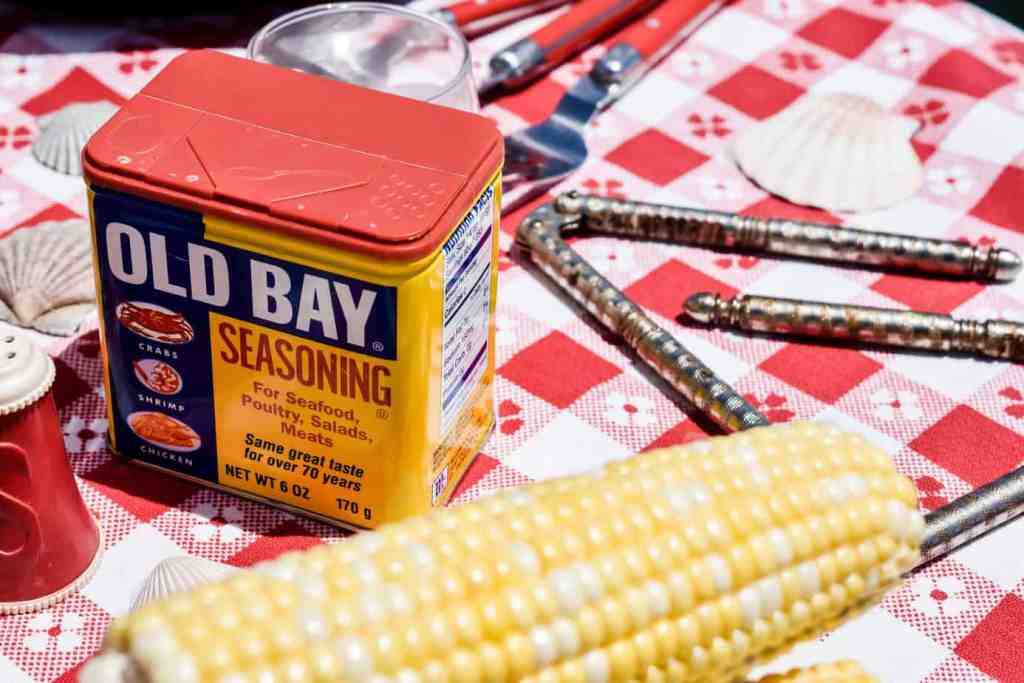 tin of old bay seasoning, corn on the cob and vintage seafood crackers