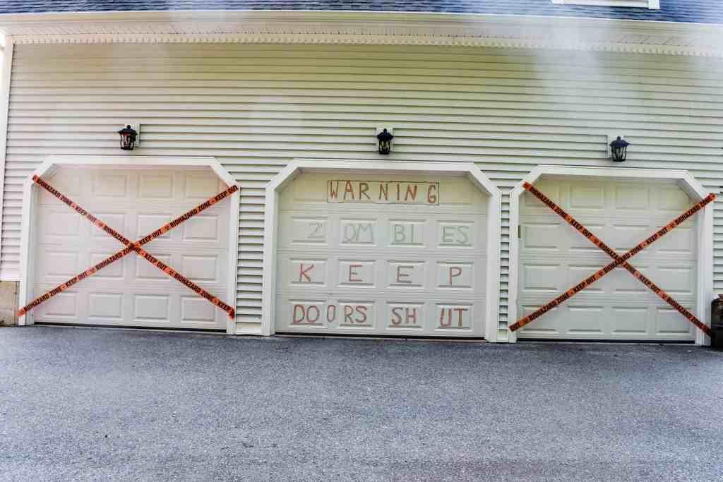 garage door halloween decorations featuring a zombie warning with garage doors strung with biohazard tape