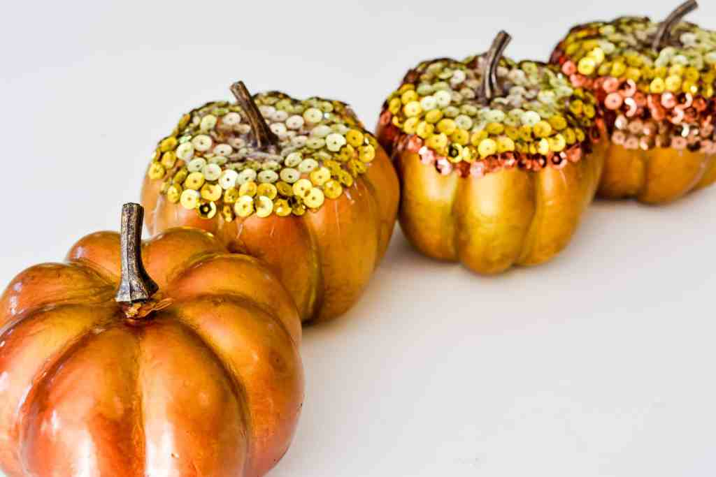 four sequin craft pumpkins lined up, three with sequins and one without